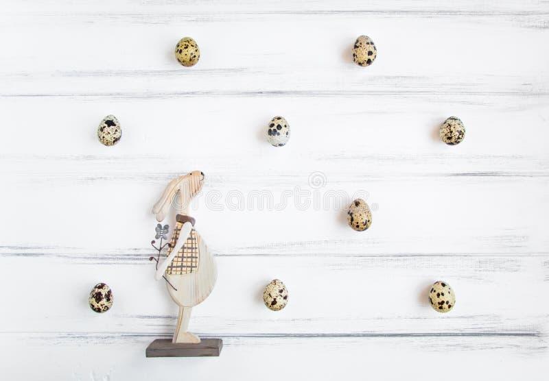 Wielkanocny świąteczny tło, przepiórek jajka w króliku na białego rocznika drewnianym stole, deseniowym i drewnianym Mieszkanie n obrazy royalty free