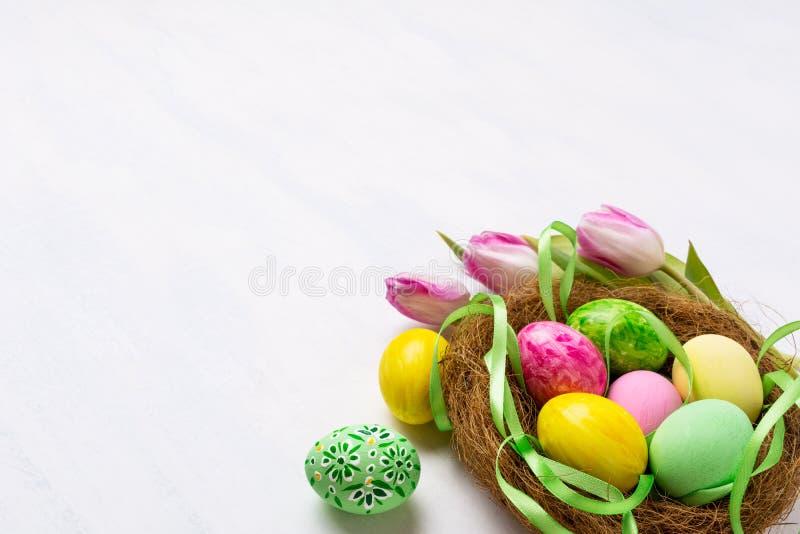 Wielkanocny centerpiece z malującymi jajkami w gniazdeczka i jedwabiu faborku obraz royalty free