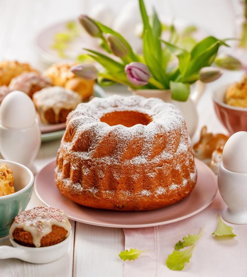 Wielkanocny drożdżowy tort kropiący z sproszkowanym cukierem na wakacyjnym stole obrazy stock