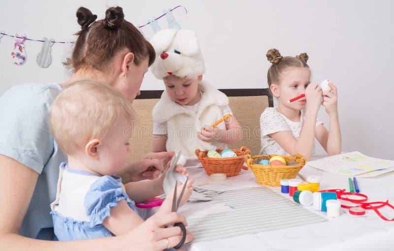 Wielkanocny festiwal: Rodzina przy stołem przygotowywa dla wakacje Córka stawia wzór na jajku fotografia stock