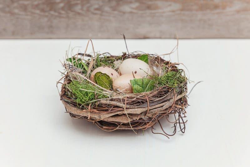 Wielkanocny jajko w gniazdeczku na nieociosanych drewnianych deskach zdjęcia royalty free