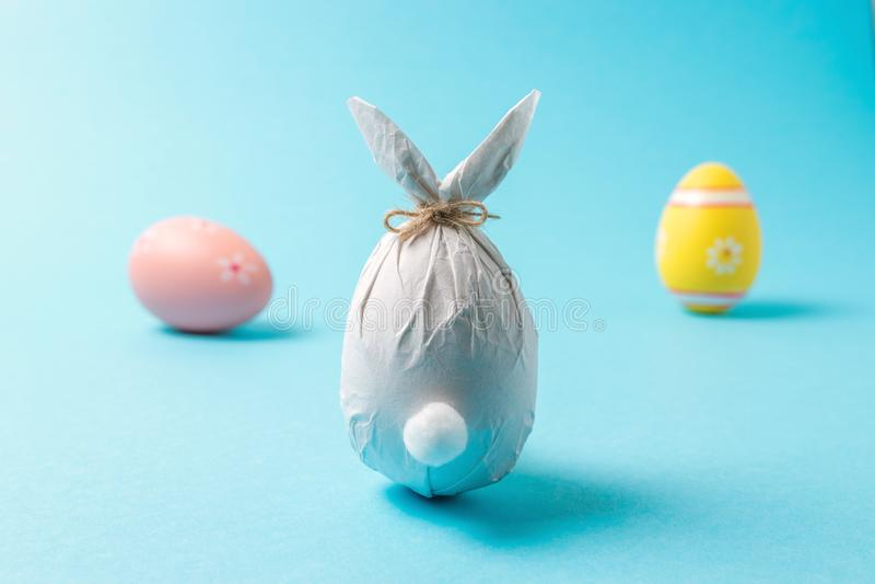 Wielkanocny jajko zawijający w papierze w formie królika z kolorowymi Wielkanocnymi jajkami Minimalny Easter pojęcie obraz stock
