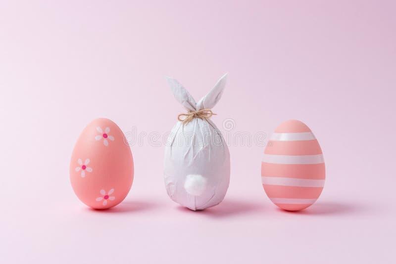 Wielkanocny jajko zawijający w papierze w formie królika z kolorowymi Wielkanocnymi jajkami Minimalny Easter pojęcie zdjęcia royalty free