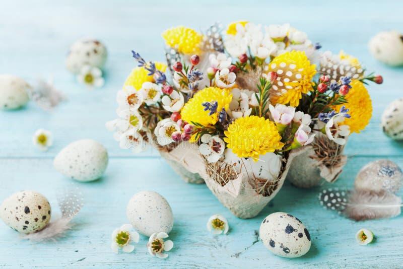 Wielkanocny kartka z pozdrowieniami z kolorowymi kwiatami, piórkiem i przepiórek jajkami na rocznika turkusu stole, Piękny wiosna obraz stock