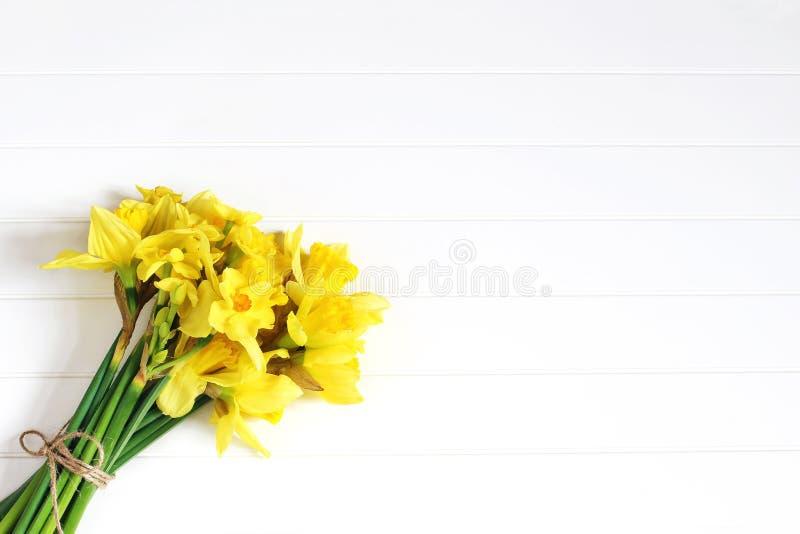 Wielkanocny kartka z pozdrowieniami, zaproszenie Bukiet żółci daffodils, narcyz kwitnie lying on the beach na białym drewnianym s zdjęcia stock