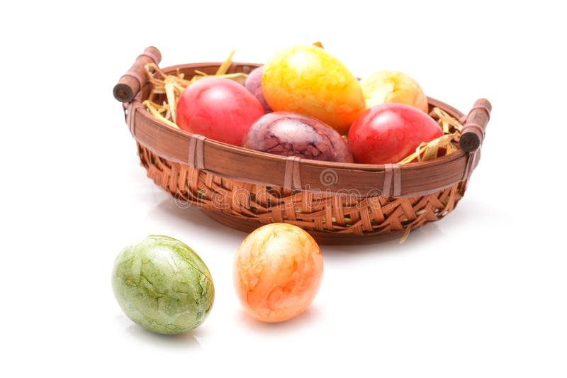 Wielkanocny kosz wypełniał z kolorowymi jajkami na białym tle zdjęcie royalty free