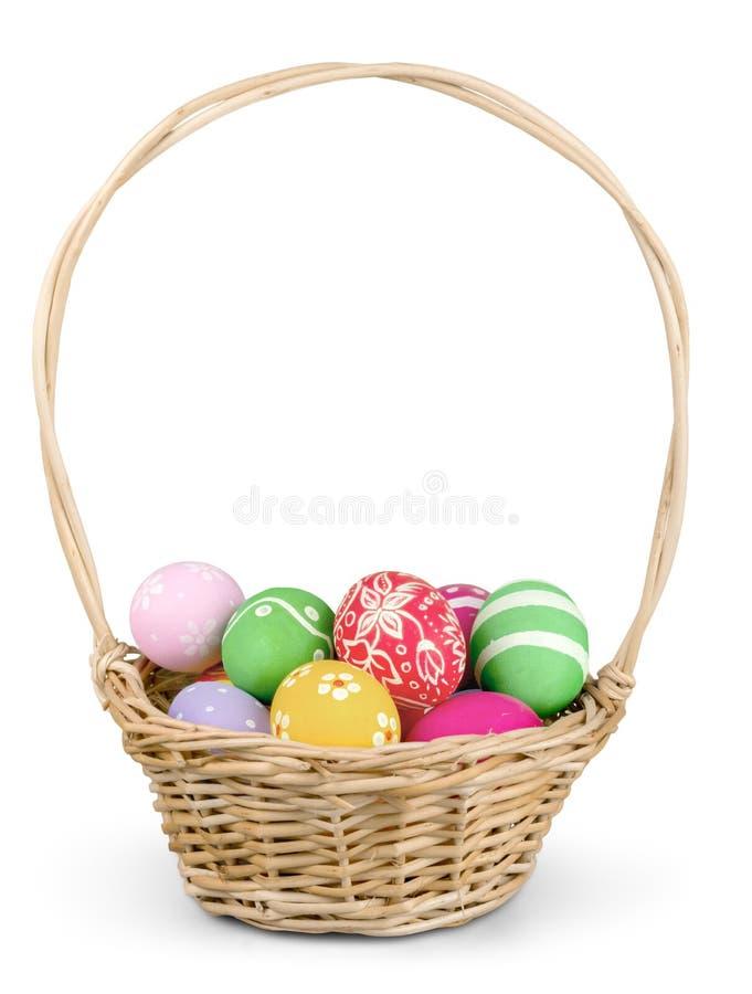 Wielkanocny kosz wypełniał z kolorowymi jajkami na bielu zdjęcie royalty free