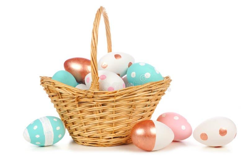 Wielkanocny kosz wypełniający z kolorowymi menchiami, błękitem, bielem i różanymi złocistymi jajkami odizolowywającymi na bielu, obraz stock