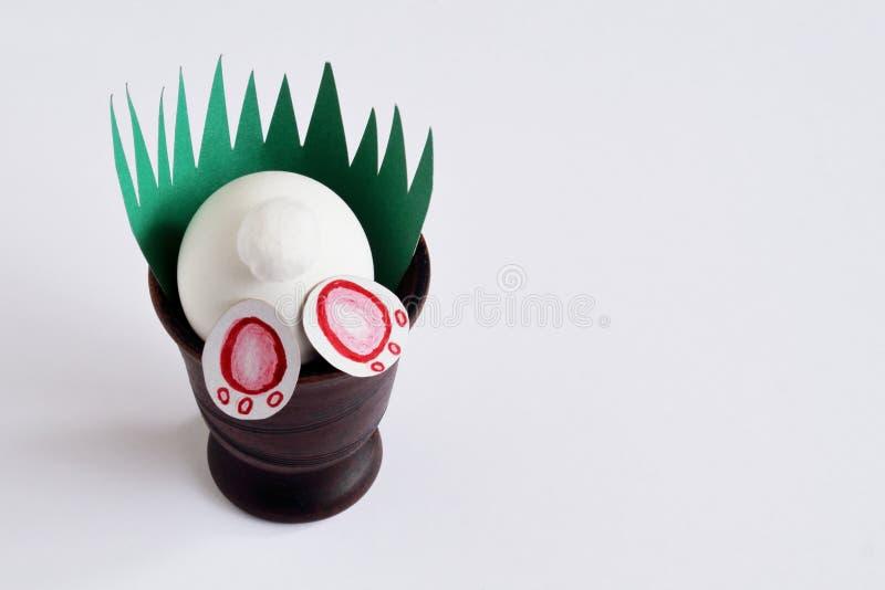 Wielkanocny niegrzeczny królik w ceramicznej wazie z zieloną trawą robić papier na lekkim tle Minimalny pojęcie dla wielkanocy zdjęcia stock