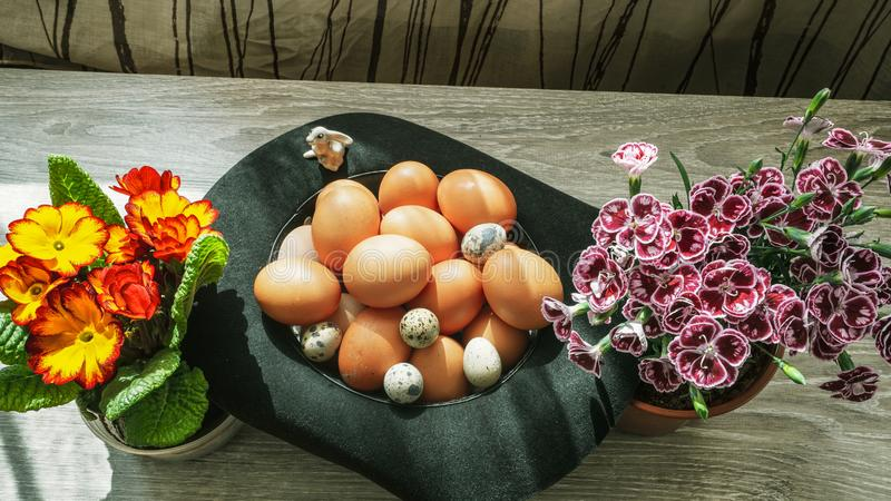 Wielkanocny prezent - kapelusz wypełniający rondo z jajkami i jaskrawymi kwiatami zdjęcie royalty free