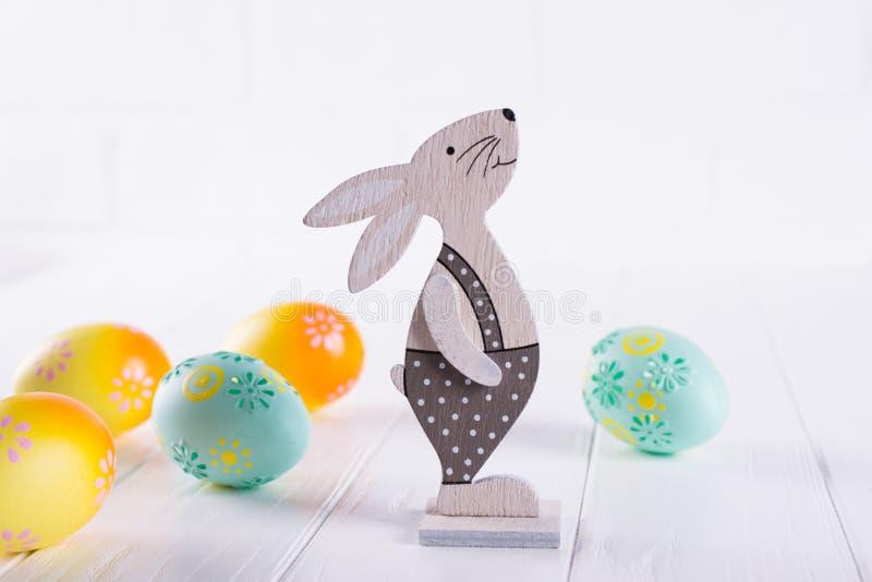 Wielkanocny skład z kolorowymi Easter jajkami, dekoracyjny drewniany królik fotografia royalty free