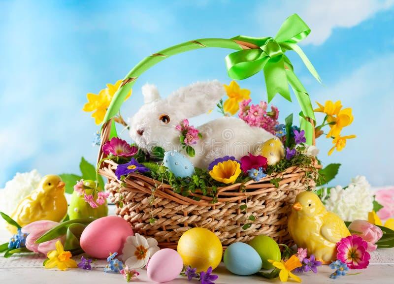 Wielkanocny skład z królikiem w koszu, wiosna kwiatach i kolorowych Wielkanocnych jajkach, obrazy royalty free