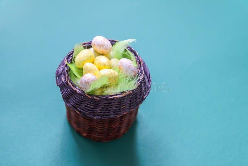 Wielkanocny skład z tradycyjnym wystrojem Mali kolorowi jajka w łozinowym koszu na miękkim tle zdjęcie royalty free