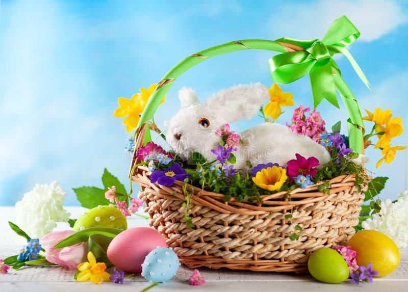 Wielkanocny skład z królikiem w koszu, wiosna kwiatach i kolorowych Wielkanocnych jajkach, obraz stock