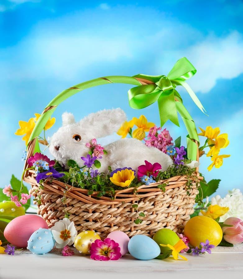 Wielkanocny skład z królikiem w koszu, wiosna kwiatach i kolorowych Wielkanocnych jajkach, fotografia stock