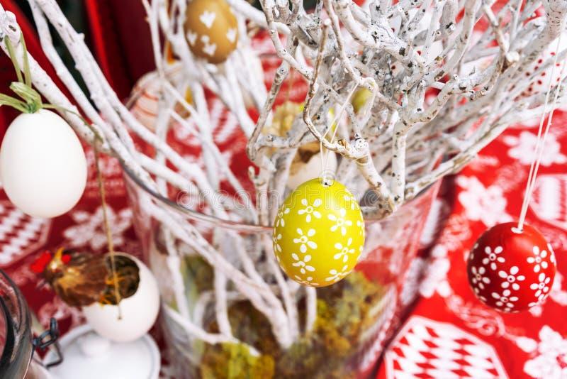 Wielkanocny skład z malującymi jajkami wiesza na wierzbie rozgałęzia się, na czerwień stołu tle, plenerowej kawiarni Zakończenie obrazy royalty free