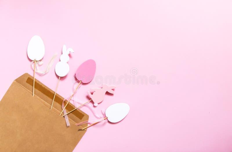 Wielkanocny skład z tradycyjnym wystrojem Dekoracyjne jajka i królika drewniane postacie w rzemiosło papieru kopercie na świetle  fotografia stock