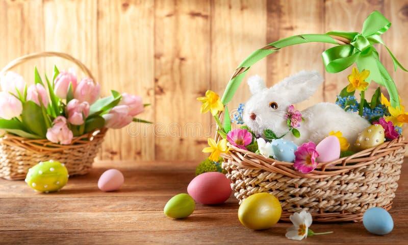 Wielkanocny sk?ad z kr?likiem w koszu, wiosna kwiatach i kolorowych Wielkanocnych jajkach, fotografia stock