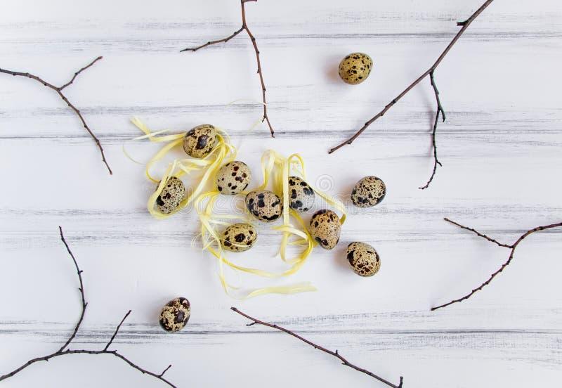 Wielkanocny tło, few przepiórek jajka dekorował na białego rocznika drewnianym stole Mieszkanie nieatutowy, odgórny widok obrazy stock