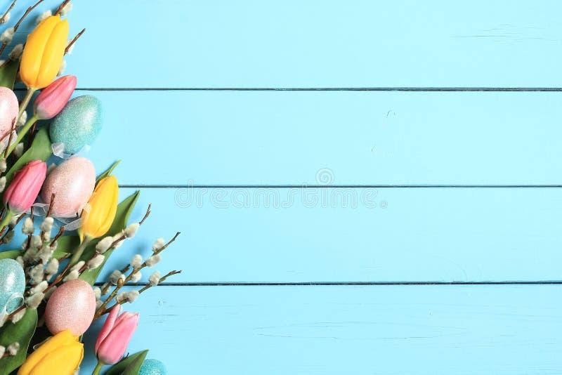 Wielkanocny tło wdowa rozgałęzia się z baziami, tulipanami i jajkami, fotografia stock