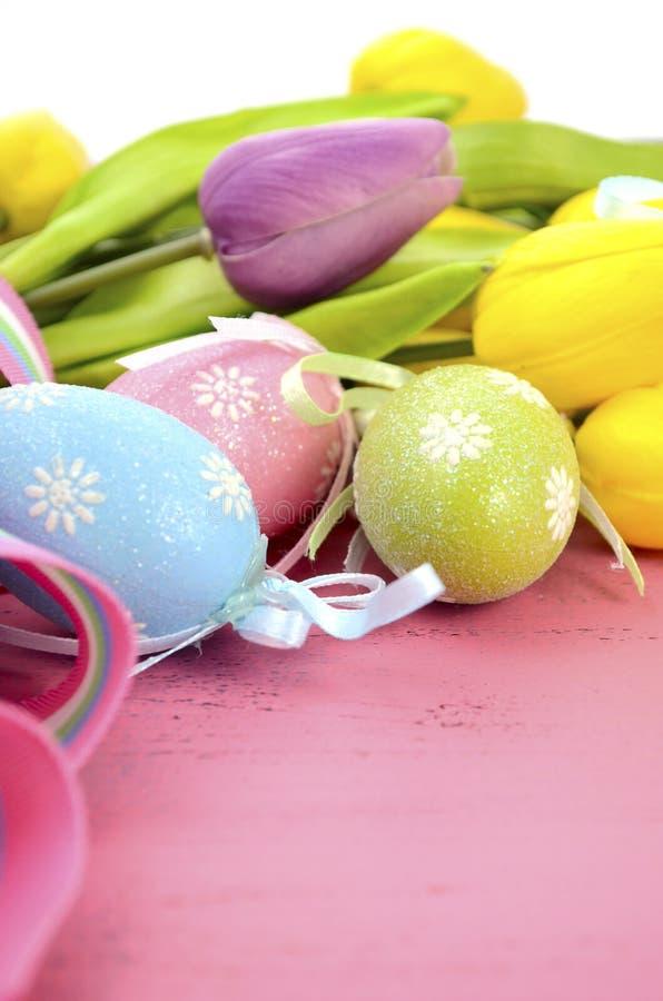 Wielkanocny tło z malującymi Wielkanocnych jajek, koloru żółtego i purpur jedwabiu tulipanami, obrazy stock