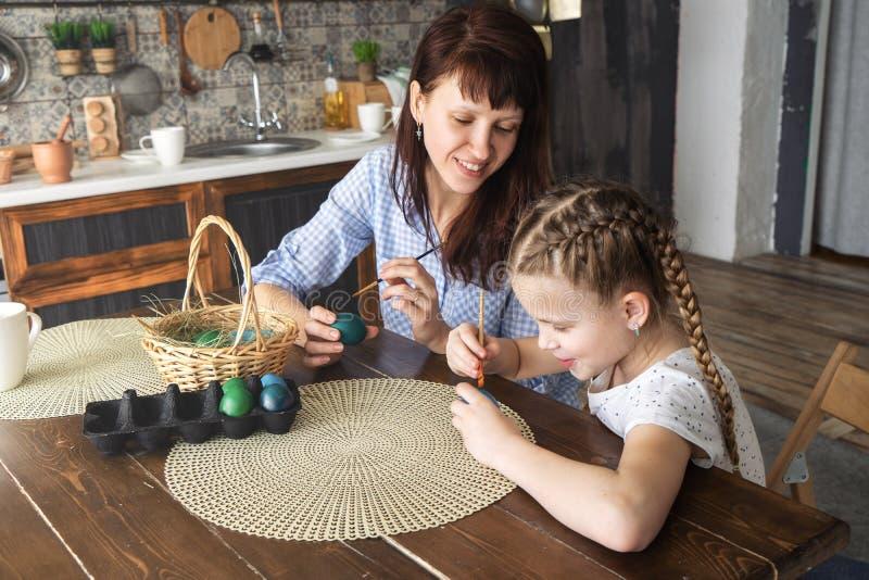 Wielkanocny wakacje: matka i córka malujemy jajka w kuchni i stawiamy one w koszu obraz stock