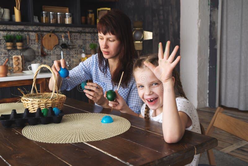 Wielkanocny wakacje: matka i córka malujemy jajka w kuchni i stawiamy one w koszu zdjęcia royalty free