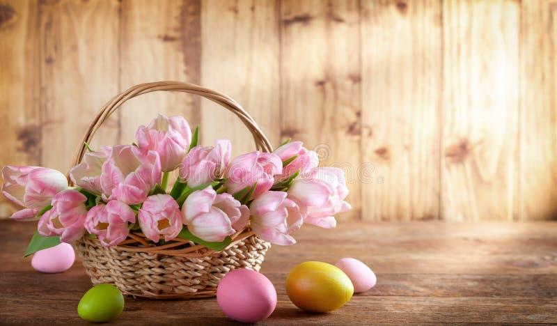 Wielkanocny wakacyjny kosz z pięknymi różowymi tulipanami i Wielkanocni jajka fotografia stock