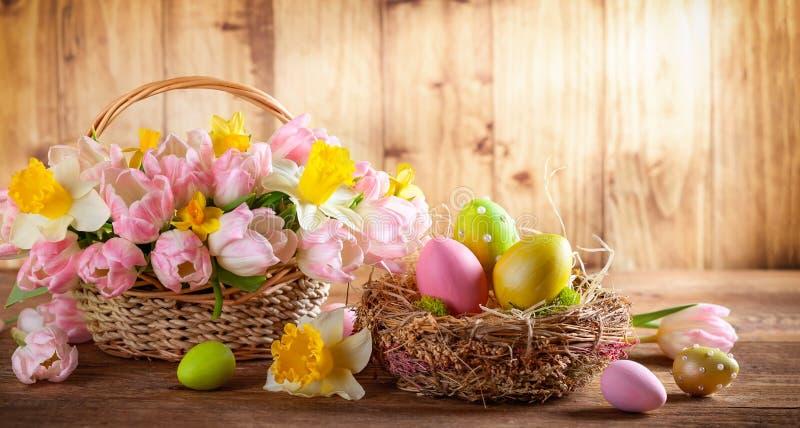 Wielkanocny wakacyjny kosz z pięknymi wiosna kwiatami i gniazdeczko z Wielkanocnymi jajkami zdjęcie stock