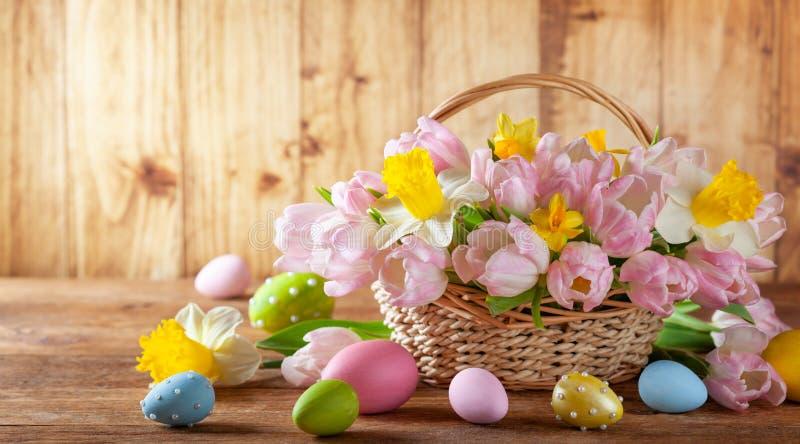 Wielkanocny wakacyjny kosz z pięknymi wiosna kwiatami i Wielkanocni jajka zdjęcie stock