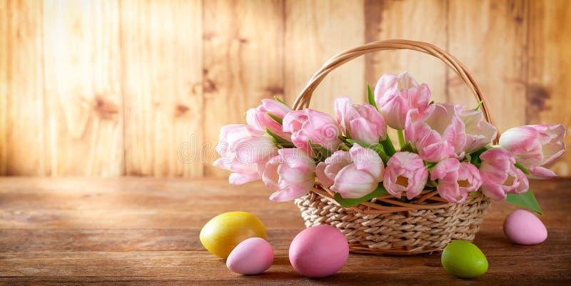 Wielkanocny wakacyjny kosz z pięknymi różowymi tulipanami i Wielkanocni jajka obraz royalty free