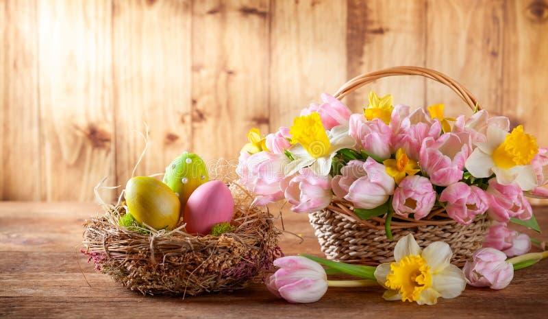 Wielkanocny wakacyjny kosz z pięknymi wiosna kwiatami i gniazdeczko z Wielkanocnymi jajkami zdjęcia royalty free