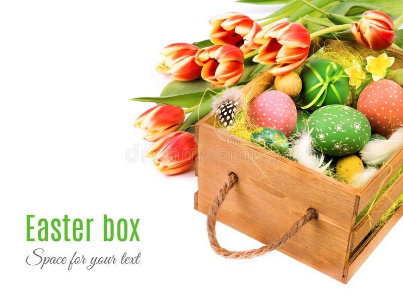 Wielkanocy pudełko z pomarańczowymi tulipanami i Wielkanocnymi jajkami na bielu obrazy royalty free