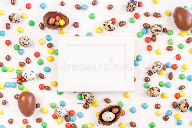 Wielkanocy rama z czekoladowymi jajkami, kolorowi cukierki obrazy royalty free