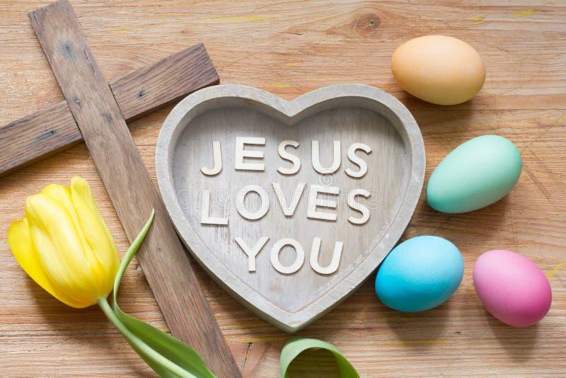 Wielkanocy serce z wpisowymi Jezusowymi miłość i krzyż ty na abstrakcjonistycznej drewnianej wiosny desce zdjęcia royalty free