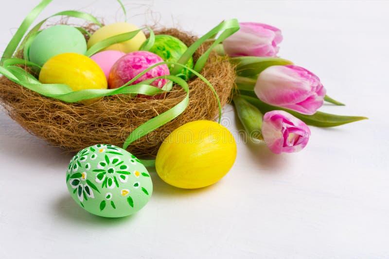 Wielkanocy stołowy centerpiece z kolorem żółtym i zielenią malował jajka w t obraz royalty free