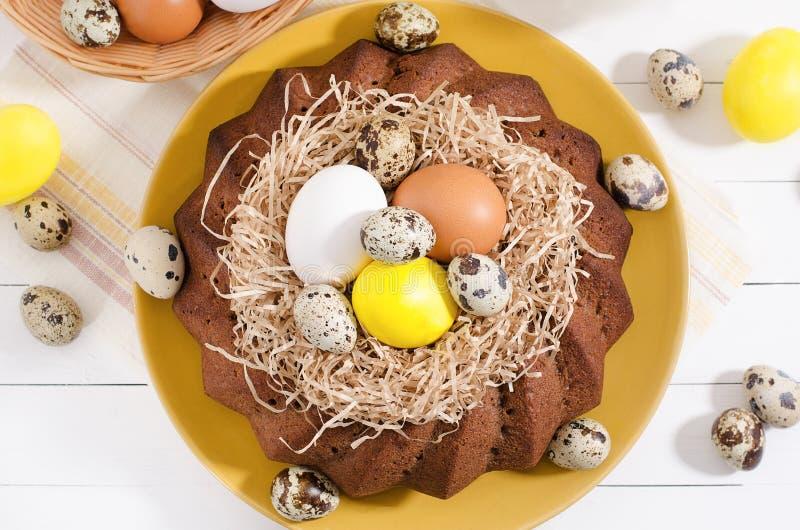Wielkanocy wciąż życie, wielkanoc tort z farbującymi jajkami w gniazdeczku, daffodi obraz stock