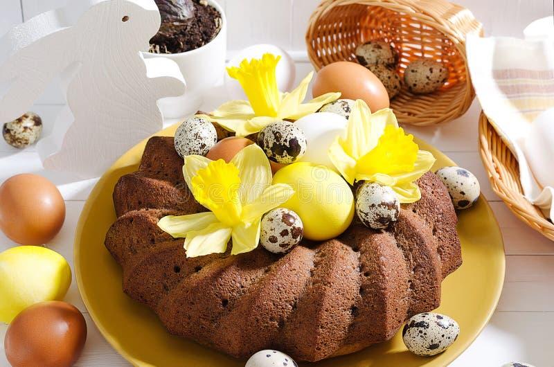 Wielkanocy wciąż życie, wielkanoc tort z farbującymi jajkami w gniazdeczku, daffodi obrazy stock