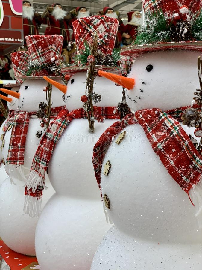 Wielki świąteczny bałwan z czerwonym szalikiem i kapeluszem stojącym w sklepie z kapeluszami Grupa śnieżna zdjęcia stock