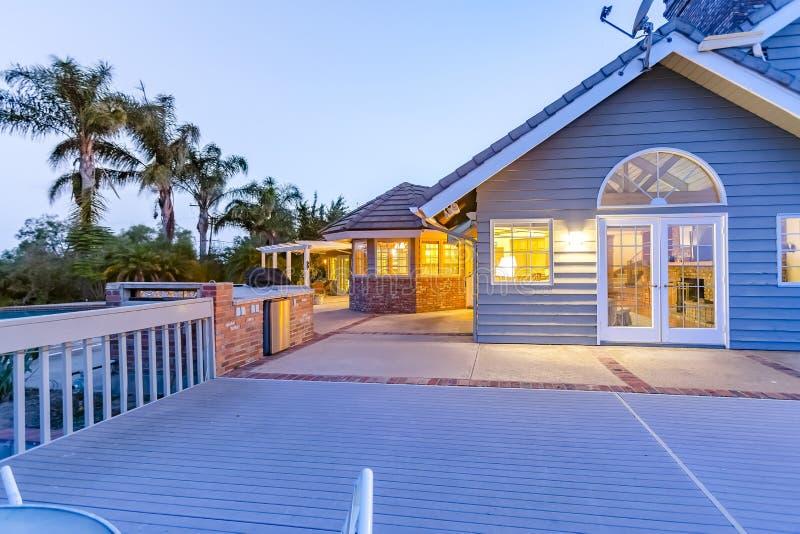 Wielki błękita dom z wielkim deckfrom podwórko przy zmierzchem fotografia stock