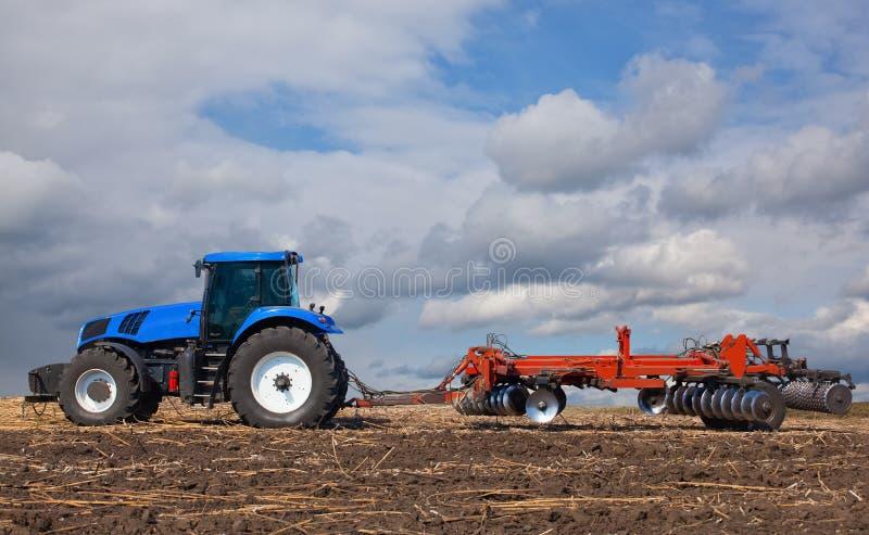 Wielki błękitny ciągnik, orze pole przeciw pięknemu niebu fotografia stock