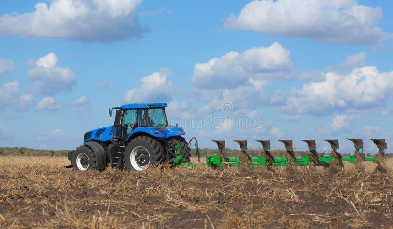 Wielki błękitny ciągnik, orze pole przeciw pięknemu niebu obraz stock