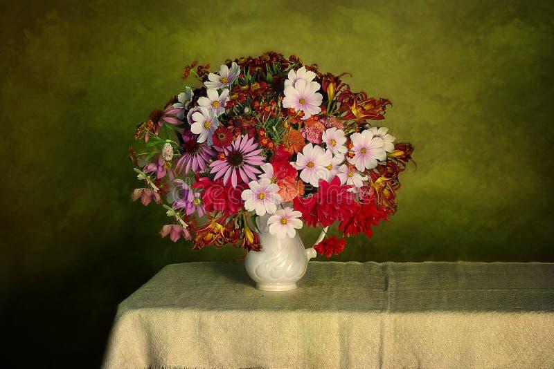 Wielki bukiet ogród kwitnie w wazie na zielonego stołu tle fotografia stock