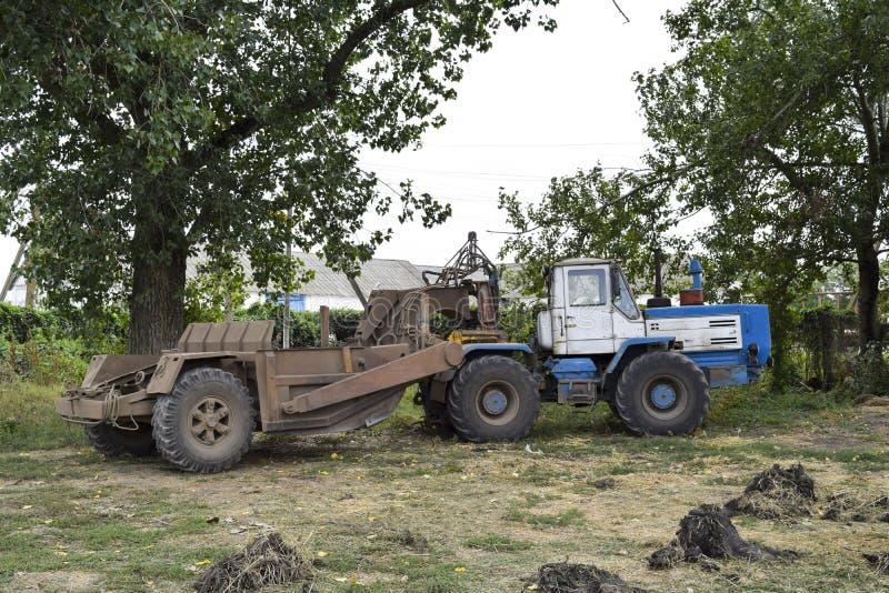 Wielki ciągnik z równiarką na przyczepie rolniczej maszynerii flancowania ikrzaka wiosna zdjęcie stock