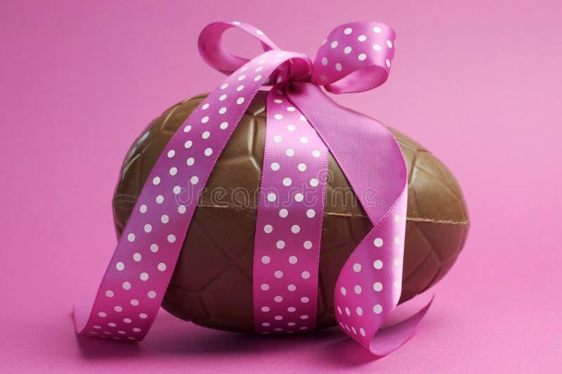 Wielki czekoladowy Wielkanocny jajko z różowym polki kropki faborkiem obrazy royalty free