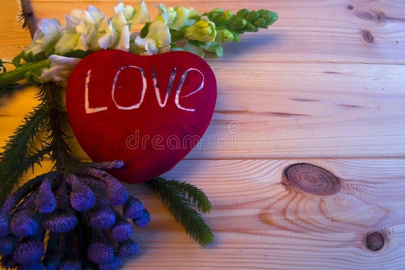 Wielki czerwony serce z pisać słowa miłością kłama na drewnianym tle zdjęcie royalty free