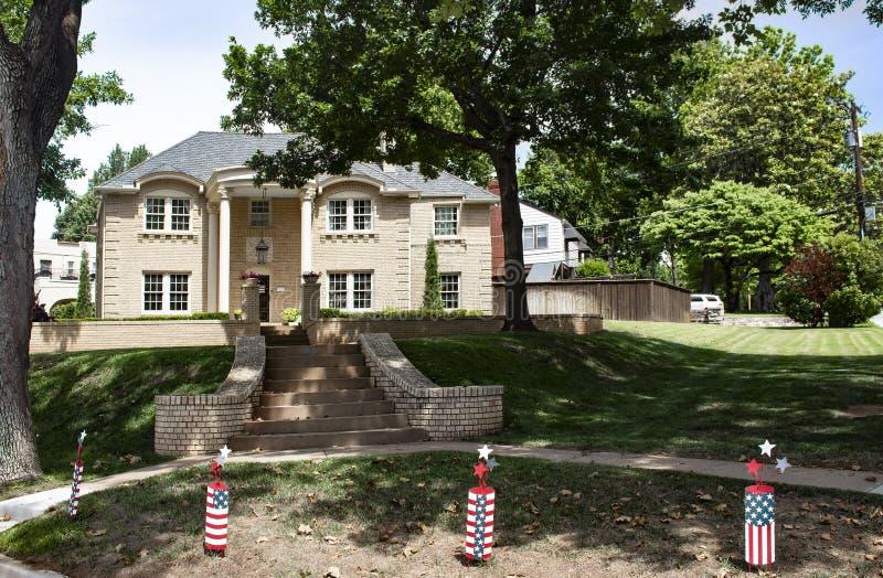 Wielki ekskluzywny cegła dom w obfitolistnym sąsiedztwie z petardą 4th Lipów ornamenty w przodzie zdjęcie royalty free