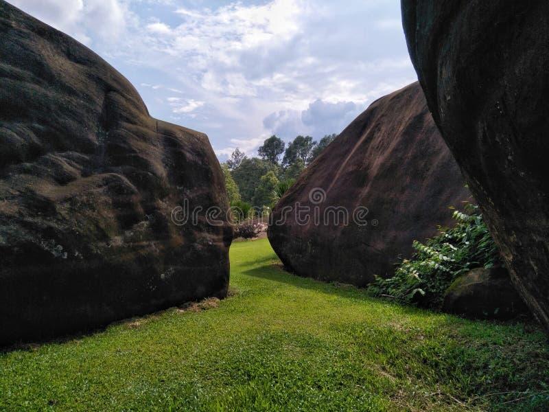 Wielki kamień na zielonym gazonie z niebem fotografia royalty free