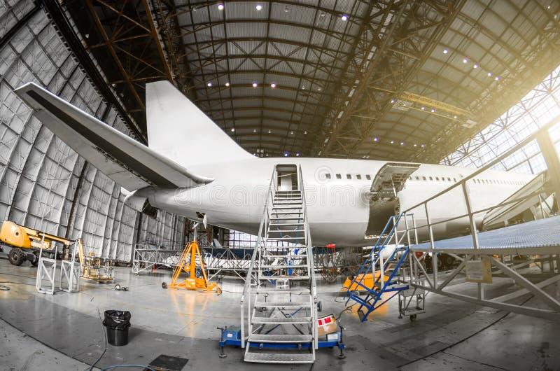 Wielki pasażerski samolot na usługa w lotnictwo hangaru tylni widoku ogon, gangway drabiny wejście obraz royalty free