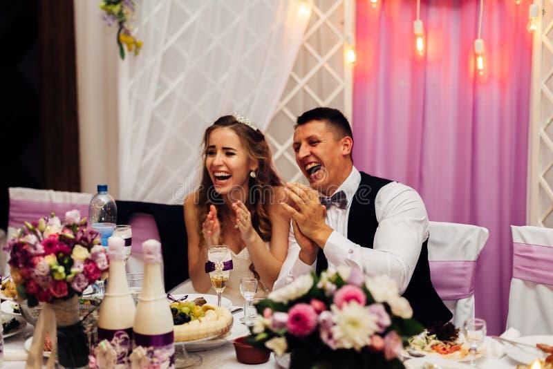Wielki portret ślubna para która siedzi przy wakacyjnym stołem, zdjęcia royalty free